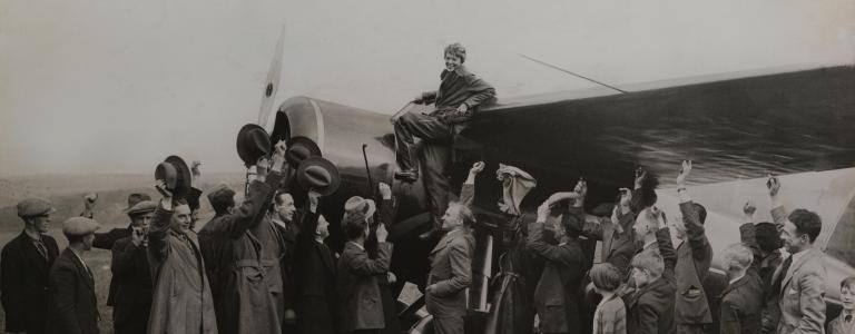 Historical photo of Amelia Earhart standing on airplane